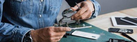 Photo pour Vue recadrée du réparateur avec loupe de maintien de tournevis près de la partie démontée du téléphone mobile sur le lieu de travail, bannière - image libre de droit