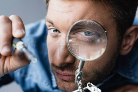 Close up view of focused repairman looking through magnifier at screwdriver on blurred foreground