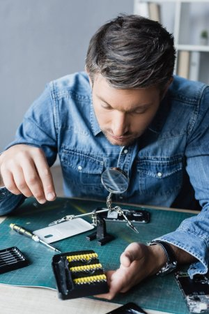 Photo for Repairman looking at holder with screwdriver bits at workplace with disassembled mobile phones on blurred background - Royalty Free Image