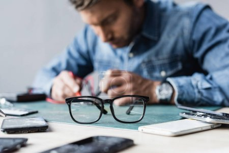 Photo for Eyeglasses on table near disassembled parts of mobile phones with blurred repairman working on background - Royalty Free Image