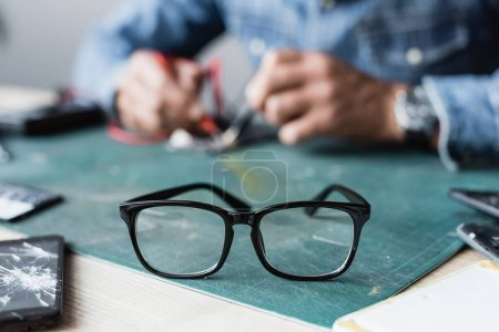 Photo for Close up view of eyeglasses with black frame on table near broken mobile phones with blurred repairman on background - Royalty Free Image