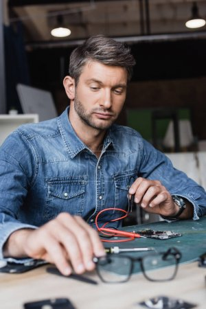 Serious repairman holding hand near eyeglasses on table with disassembled parts of mobile phone on blurred foreground