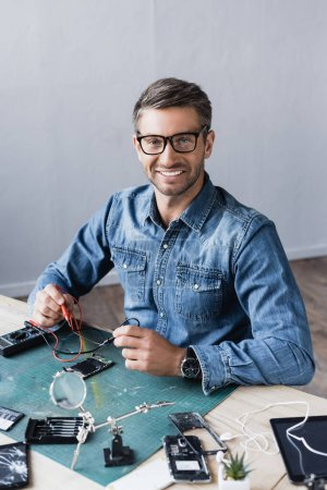 Photo for Happy repairman looking at camera with sensors of multimeter while sitting at table with disassembled parts of smartphones - Royalty Free Image