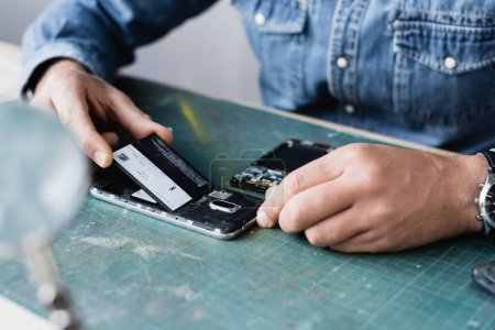 Photo for Cropped view of repairman putting battery in mobile phone on table with blurred magnifier on foreground - Royalty Free Image