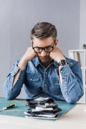 Photo for Thoughtful repairman with hands near cheeks sitting at table wit blurred pile of broken mobile phones on foreground - Royalty Free Image
