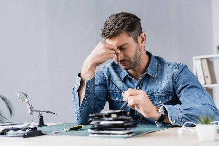 Tired repairman with hand near closed eyes sitting at workplace with pile of broken mobile phones on blurred foreground