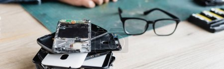 Close up view of pile of broken mobile phones near eyeglasses on workplace with blurred repairman on background, banner