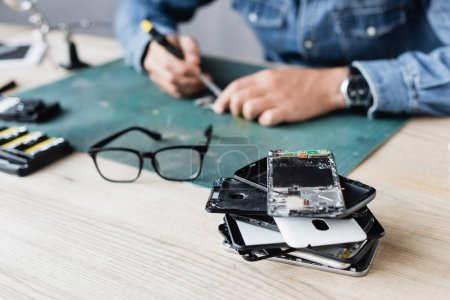 Photo for Close up view of pile with broken mobile phones near eyeglasses on workplace with blurred repairman working on background - Royalty Free Image
