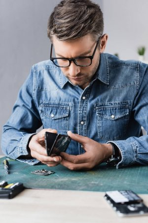 Focused repairman disassembling broken smartphone on workplace on blurred foreground