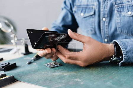 Photo for Close up view of disassembled parts of broken smartphone in hands of repairman at workplace on blurred background - Royalty Free Image