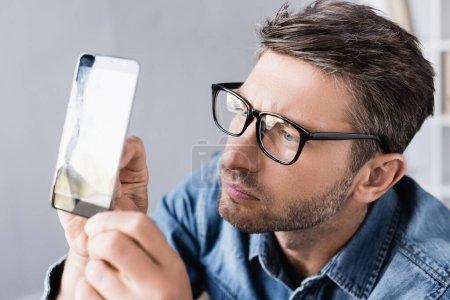 Photo for Focused repairman in eyeglasses looking at broken touchscreen in office - Royalty Free Image