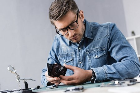 Photo for Focused repairman disassembling broken smartphone while sitting at workplace with magnifier on blurred foreground - Royalty Free Image