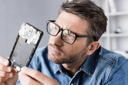 Concentrated repairman in eyeglasses looking at disassembled part of mobile phone on blurred foreground