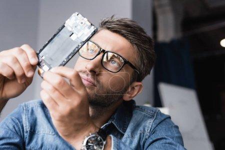 Photo pour Réparateur concentré dans les lunettes regardant composant démonté de téléphone mobile sur fond flou - image libre de droit