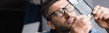Photo pour Réparateur concentré en lunettes regardant une partie démontée d'un téléphone portable cassé sur fond flou, bannière - image libre de droit