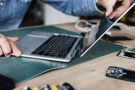 Photo for Cropped view of repairman holding damaged laptop at workplace on blurred background - Royalty Free Image