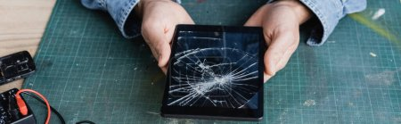 Cropped view of repairman holding smashed digital tablet at workplace, banner