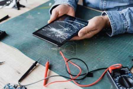 Cropped view of repairman holding smashed digital tablet near multimeter at workplace