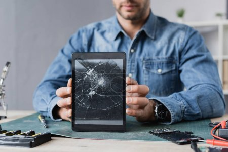Photo for Cropped view of repairman showing smashed digital tablet, while sitting at workplace - Royalty Free Image