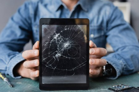 Close up view of smashed digital tablet in hands of repairman at workplace on blurred background