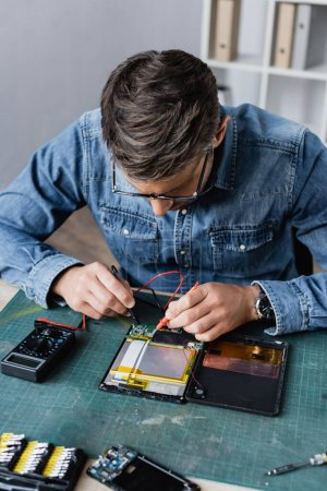 Photo for Repairman with holding sensors of multimeter on broken part of digital tablet at workplace - Royalty Free Image