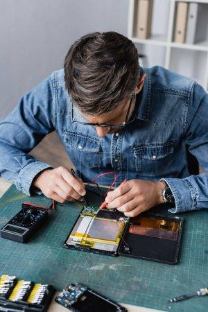 Photo pour Réparateur avec capteurs de maintien du multimètre sur la partie cassée de la tablette numérique sur le lieu de travail - image libre de droit