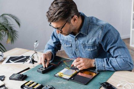 Photo pour Réparateur réglant le multimètre tout en tenant les capteurs près de la partie démontée de la tablette numérique cassée sur le lieu de travail - image libre de droit