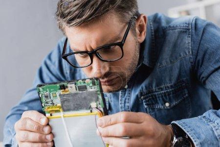 Photo for Focused repairman in eyeglasses looking at part of broken digital tablet - Royalty Free Image