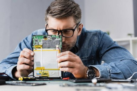 Photo for Focused repairman squinting, while looking at part of broken digital tablet with blurred workplace on foreground - Royalty Free Image