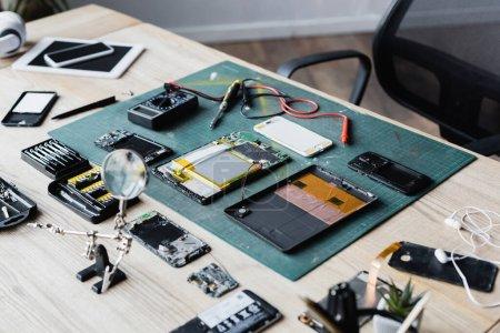 Photo pour Pose plate de pièces démontées de dispositifs, multimètre, tournevis et loupe sur le lieu de travail - image libre de droit