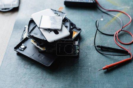 Photo pour Vue rapprochée téléphones démontés pile près de multimètre sur le lieu de travail sur fond flou - image libre de droit