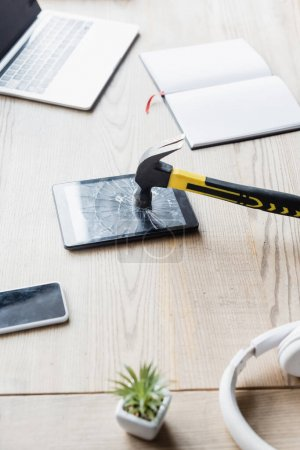 Hammer on smashed digital tablet near headphones and blank notebook on table with digital devices