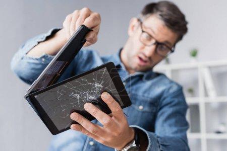 Surprised businessman disassembling smashed digital tablet on blurred background