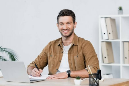 Photo for Smiling businessman looking at camera while writing in notebook at workplace with laptop on blurred background - Royalty Free Image