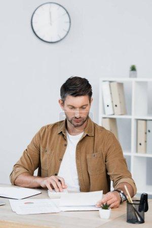 Photo pour Homme d'affaires concentré regardant la feuille de papier tout en comptant sur la calculatrice sur le lieu de travail sur fond flou - image libre de droit