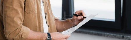 Photo pour Vue recadrée de l'homme d'affaires debout et écrivant sur le document avec fenêtre floue sur fond, bannière - image libre de droit