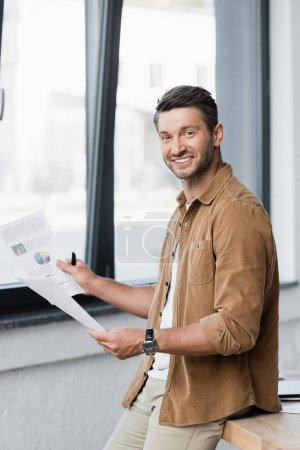 Photo for Smiling businessman with paper sheets looking at camera while leaning on table with blurred window on background - Royalty Free Image