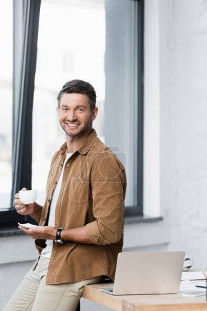 Photo pour Homme d'affaires joyeux avec tasse de café et soucoupe regardant la caméra tout en s'appuyant sur la table avec ordinateur portable sur fond flou - image libre de droit
