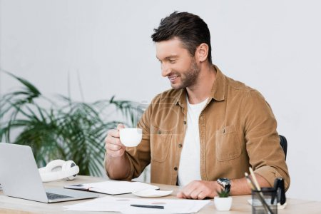 Photo for Cheerful businessman with coffee cup looking at laptop while sitting at workplace with blurred plant on background - Royalty Free Image