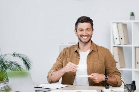 Photo pour Homme d'affaires joyeux avec soucoupe tasse de café nad regardant la caméra tout en étant assis sur le lieu de travail sur le premier plan flou - image libre de droit
