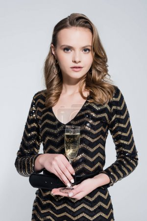 young woman holding glass of champagne isolated on grey
