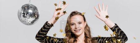 Photo pour Joyeuse jeune femme debout près de boule disco et tombant confettis sur gris, bannière - image libre de droit