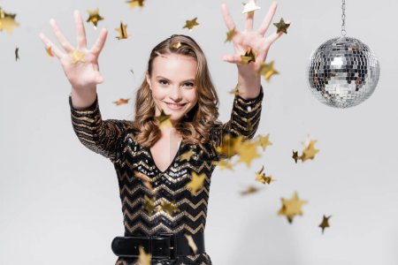 happy young woman standing near disco ball and throwing confetti on grey