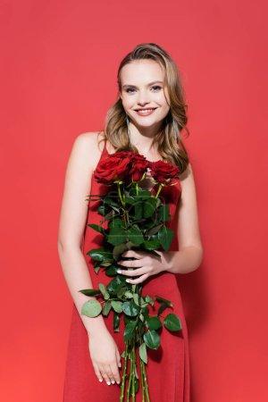 Photo pour Heureuse jeune femme regardant caméra et tenant des roses sur rouge - image libre de droit