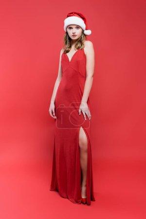 longueur pleine de femme élégante en robe et chapeau santa debout sur le rouge