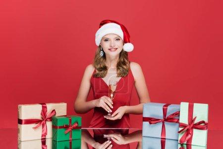 Photo pour Femme heureuse dans le chapeau santa tenant verre de champagne près de roses et cadeaux de Noël sur rouge - image libre de droit