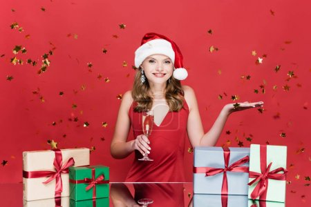 Photo for Happy woman in santa hat holding glass of champagne and pointing with hand near christmas presents and falling confetti on red - Royalty Free Image
