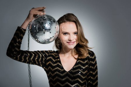 Photo for Positive young woman looking at camera while holding disco ball on grey - Royalty Free Image