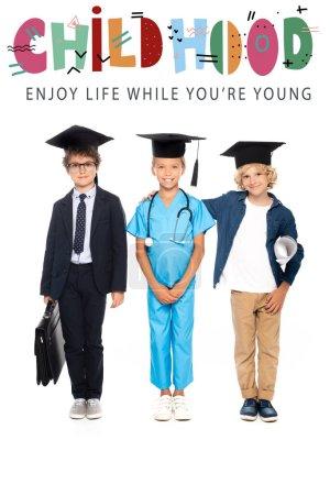 Photo pour Enfants en casquettes de fin d'études vêtus de costumes de différentes professions debout près de l'enfance, profiter de la vie pendant que vous êtes jeune lettrage sur blanc - image libre de droit