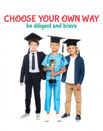 Photo pour Enfants en casquettes de graduation vêtus de costumes de différentes professions tenant trophée d'or près de choisir votre propre façon être diligent et courageux lettrage sur blanc - image libre de droit